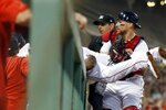 Boston Red Sox's Michael Chavis makes a catch on a pop foul by Los Angeles Dodgers' Enrique Hernandez over the dugout rail as Christian Vazquez, right, holds his legs during the fourth inning of a baseball game in Boston, Sunday, July 14, 2019. (AP Photo/Michael Dwyer)