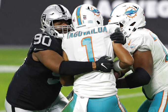 Las Vegas Raiders defensive tackle Johnathan Hankins (90) sacks Miami Dolphins quarterback Tua Tagovailoa (1) during the second half of an NFL football game, Saturday, Dec. 26, 2020, in Las Vegas. (AP Photo/Steve Marcus)