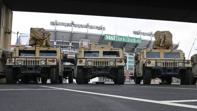 A number of armored transports sit parked in the lot between Camden Yards and M&T Bank Stadium in Baltimore, M.D. The National Guard has been deployed in Maryland. (Ulysses Muñoz/The Baltimore Sun via AP)