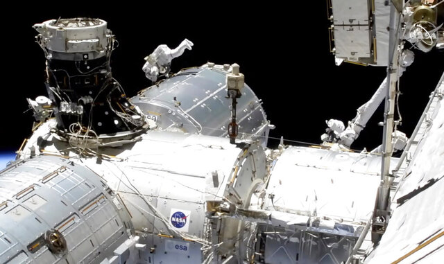 In this image taken from NASA video, NASA astronaut Mike Hopkins works outside the International Space Station's European lab on Wednesday, Jan. 27, 2021. Hopkins and Victor Glover went spacewalking Wednesday to install a high-speed data link outside the International Space Station's European lab and connect cables for an experiment platform awaiting activation for almost a year. (NASA via AP)