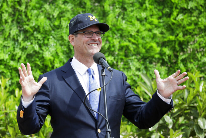 FILE - In this April 26, 2017, file photo, Michigan head football coach Jim Harbaugh talks to journalists during a press conference, in Rome. Harbaugh is taking Michigan's football team to South Africa in May. Director of football operations Mark Taurisani tweeted about the trip Tuesday, Feb. 19, 2019. Like last year's visit to France, the Wolverines will not practice in South Africa. Harbaugh did have practices in Italy in 2017. (AP Photo/Andrew Medichini, File)