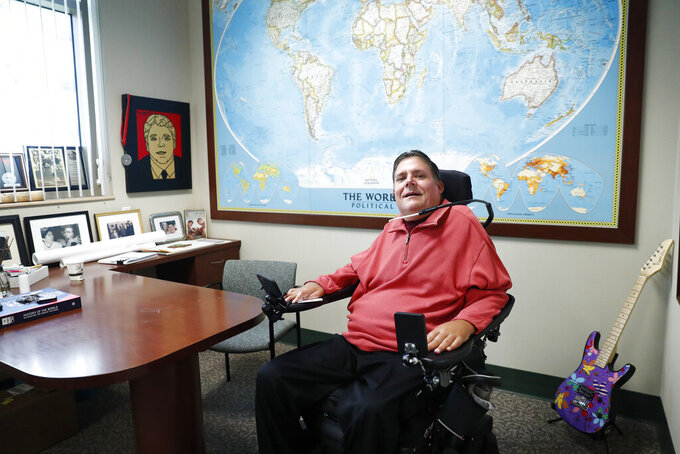 In this Wednesday, Jan. 22, 2020 photo, Marc Buoniconti, who was paralyzed from the shoulders down making a tackle in college in 1985, poses for a portrait in his office at the The Miami Project to Cure Paralysis in Miami. As the Super Bowl returns to Miami this week, Marc has mixed feelings about the sport. (AP Photo/Brynn Anderson)
