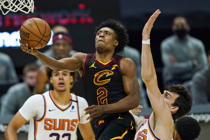 Cleveland Cavaliers' Collin Sexton, left, drives to the basket against Phoenix Suns' Dario Saric in the second half of an NBA basketball game, Tuesday, May 4, 2021, in Cleveland. (AP Photo/Tony Dejak)