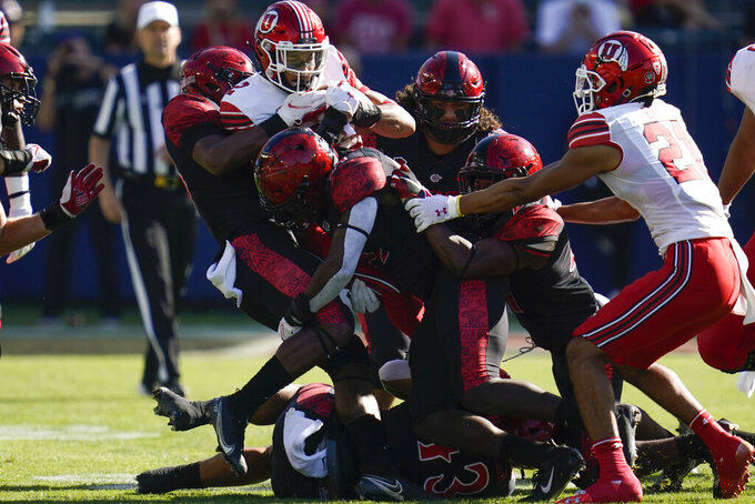 Utah running back Micah Bernard (2) is tackled by San Diego State defenders during the first half of an NCAA college football game Saturday, Sept. 18, 2021, in Carson, Calif. (AP Photo/Ashley Landis)