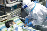 FILE - In this Jan. 24, 2020, file photo, released by China's Xinhua News Agency, a medical worker attends to a patient in the intensive care unit at Zhongnan Hospital of Wuhan University in Wuhan in central China's Hubei Province. The Chinese city of Wuhan is looking back on a year since it was placed under a 76-day lockdown beginning Jan. 23, 2020. (Xiong Qi/Xinhua via AP, File)