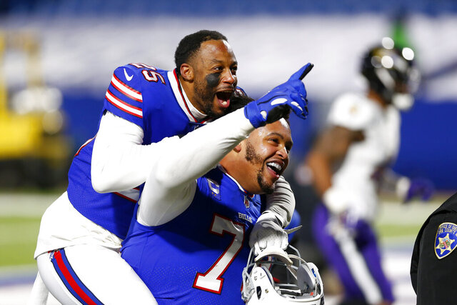 Buffalo Bills' Taiwan Jones (25) celebrates with Dion Dawkins (73) after an NFL divisional round football game against the Baltimore Ravens Saturday, Jan. 16, 2021, in Orchard Park, N.Y. The Bills won 17-3. (AP Photo/John Munson)