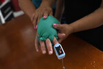 "Two latex gloves filled with warm water cover the hand of the husband of nurse Lidiane Melo as she demonstrates at their home in Rio de Janeiro, Brazil, Wednesday, April 14, 2021. In the early days of the pandemic, as sufferers were calling out for comfort that she was too busy to provide, Melo put water-filled gloves on patients' hands to simulate a loving touch. Some have christened the practice the ""hand of God,"" and it is now the searing image of a nation roiled by a medical emergency with no end in sight. (AP Photo/Silvia Izquierdo)"