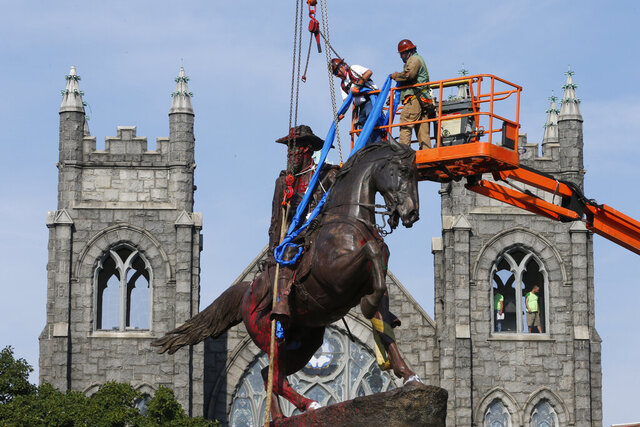 Crews attach straps to the statue Confederate General J.E.B. Stuart on Monument Avenue Tuesday July 7, 2020, in Richmond, Va. The statue is one of several that will be removed by the city as part of the Black Lives Matter reaction. (AP Photo/Steve Helber)