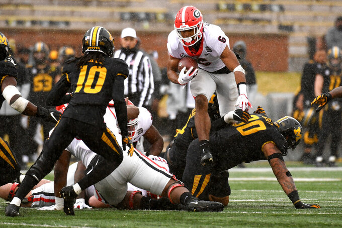 Georgia running back Kenny McIntosh (6) leaps over Missouri defensive lineman Markell Utsey as Missouri defensive back Chris Mills (10) defends during the second half of an NCAA college football game Saturday, Dec. 12, 2020, in Columbia, Mo. Georgia won 49-14. (AP Photo/L.G. Patterson)