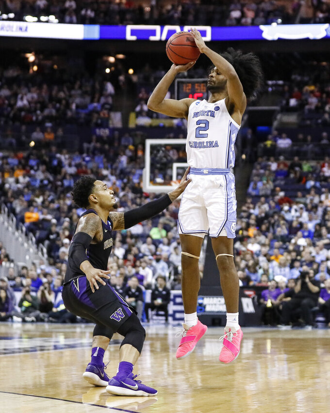North Carolina's Coby White (2) shoots over Washington's David Crisp, left, in the second half during a second-round men's college basketball game in the NCAA Tournament, Sunday, March 24, 2019, in Columbus, Ohio. (AP Photo/John Minchillo)