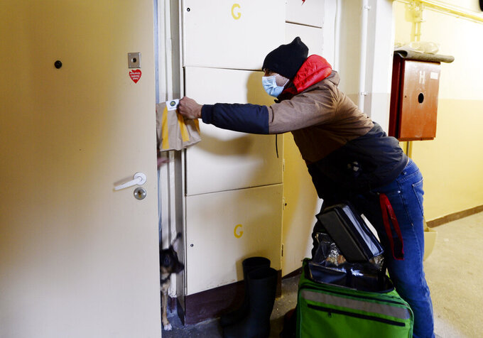 Anonymous behind his anti-COVID-19 mask, Venezuela's 2012 Olympic champion in fencing, Ruben Limardo Gascon, delivers food to clients who had ordered it thourgh Uber Eats in Lodz, Poland, Saturday, Nov. 14, 2020. In Poland, where he has lived for years, GAscon delivers food for Uber Eats to support his family as he trains for the Olympics in Tokyo next summer.(AP Photo/Czarek Sokolowski)