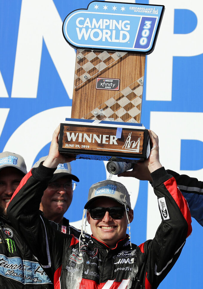 Cole Custer holds up the trophy in Victory Lane after winning the NASCAR Xfinity Series auto race at Chicagoland Speedway in Joliet, Ill., Saturday, June 29, 2018. (AP Photo/Nam Y. Huh)