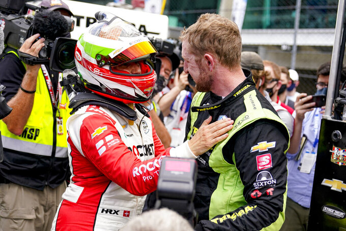 Simona De Silvestro of Switzerland, left, consoles Charlie Kimball after he failed to make the field during the last row qualifications for the Indianapolis 500 auto race at Indianapolis Motor Speedway in Indianapolis, Sunday, May 23, 2021. (AP Photo/Michael Conroy)