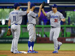 Los Angeles Dodgers players Logan Forsythe (11), Chris Taylor, center, and Joc Pederson (31) celebrate after the Dodgers defeated the Miami Marlins 7-0 in a baseball game, Thursday, May 17, 2018, in Miami. (AP Photo/Wilfredo Lee)