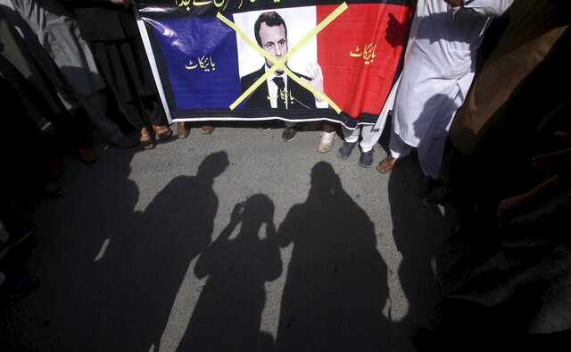 Supporters of the religious student group, Islami Jamiat Tulba, hold a representation of the French flag with a defaced image of French President Emmanuel Macron and Urdu writing which reads,