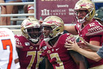 Florida State's Cam Akers, center celebrates with teammates Alex Hornibrook, right, and Darius Washington after scoring against Syracuse during the first quarter of an NCAA college football game, Saturday, Oct. 26, 2019, in Tallahassee Fla. (AP Photo/Steve Cannon)