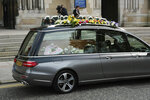 The hearse carrying the body of journalist Lyra McKee arrives at St Anne's Cathedral in Belfast, northern Ireland, Wednesday April 24, 2019. The leaders of Britain and Ireland will join hundreds of mourners Wednesday at the funeral of Lyra McKee, the young journalist shot dead during rioting in Northern Ireland last week. (Liam McBurney/PA via AP)
