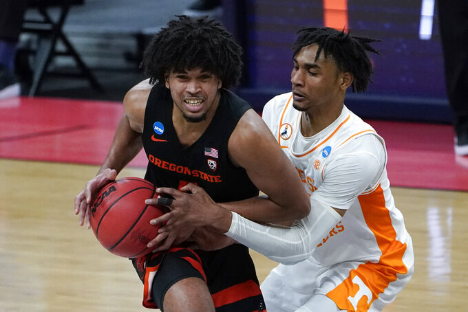 Tennessee guard Keon Johnson, right, fouls Oregon State guard Ethan Thompson (5) during the second half of a men's college basketball game in the first round of the NCAA tournament at Bankers Life Fieldhouse in Indianapolis, Friday, March 19, 2021. Oregon State won 70-56. (AP Photo/Paul Sancya)