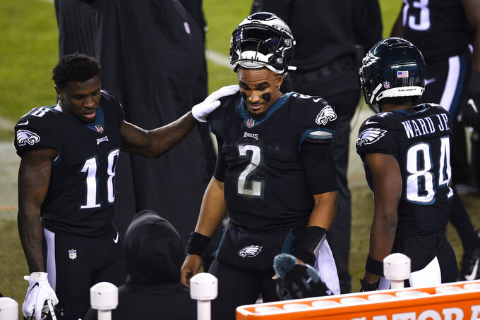 Philadelphia Eagles' Jalen Hurts (2) stands on the sidelines with Jalen Reagor (18) and Greg Ward (84) after a fumble during the second half of an NFL football game against the New Orleans Saints, Sunday, Dec. 13, 2020, in Philadelphia. (AP Photo/Derik Hamilton)