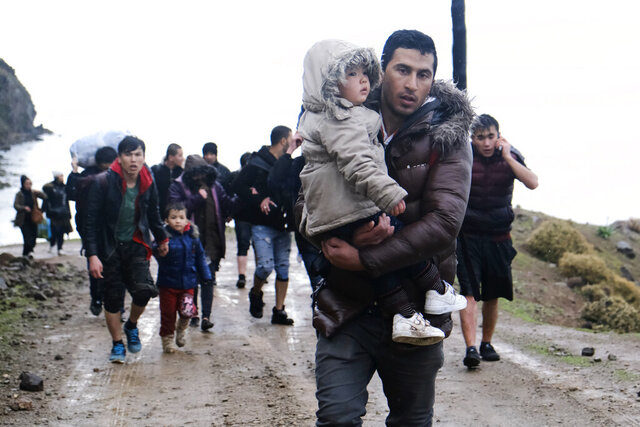FILE  - In this March 5 2020 file photo, migrants walk to the village of Skala Sikaminias, on the Greek island of Lesbos, after crossing on a dinghy the Aegean sea from Turkey on Thursday, March 5, 2020. No entry, says Hungary. Move along, says Greece. Watch out, says Croatia: They might have the coronavirus. This week, thousands of asylum-seekers sit at the intersection of a pair of fast-moving news stories — a spike in migration in Europe and uncertainty about the global spread of the new and sometimes deadly virus. (AP Photo/Alexandros Michailidis, File)