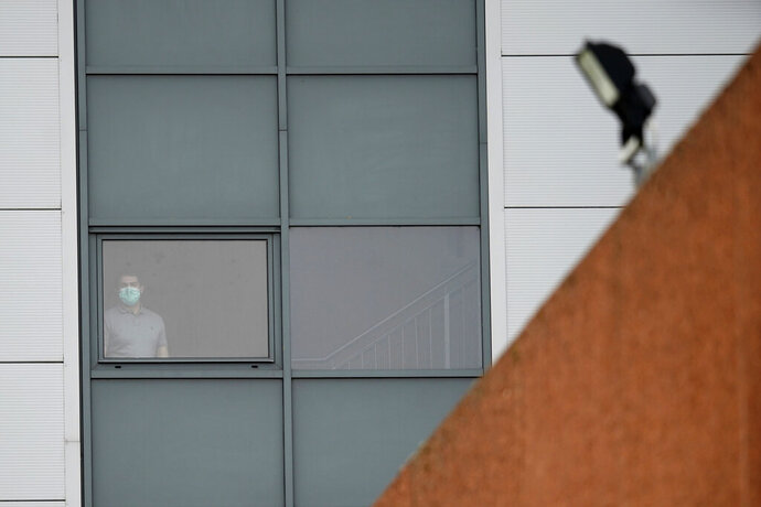 A person wearing a mask stands at a window of a staff accommodation block where British nationals recently flown back from China and at risk from the new virus are being quarantined, at Arrowe Park Hospital, on the Wirral, in Liverpool, England, Wednesday Feb. 5, 2020. Britain on Tuesday urged all of its citizens in China to leave the country because of the outbreak of a respiratory illness from a new virus, while Belgium became the latest nation to announce a confirmed case. (AP Photo/Jon Super)