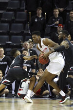 Cincinnati's Cane Broome, left, and Eliel Nsoeme keep heavy coverage over Houston's Chris Harris Jr. in the first half of an NCAA college basketball American Athletic Conference championship game Sunday, March 17, 2019, in Memphis, Tenn. (AP Photo/Troy Glasgow)