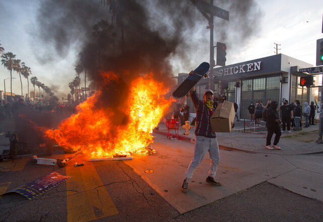 A protester shouts in front of a fire during a protest over the death of George Floyd, a handcuffed black man in police custody in Minneapolis, in Los Angeles, Saturday, May 30, 2020. (AP Photo/Ringo H.W. Chiu)