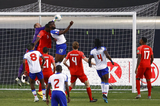 Canada's Milan Borjan , top left, and Doniel Henry (15) defend against Haiti's Frantzdy Pierrot (20) during the first half of a World Cup qualifying soccer match Tuesday, June 15, 2021, in Bridgeview, Ill. (AP Photo/Kamil Krzaczynski)