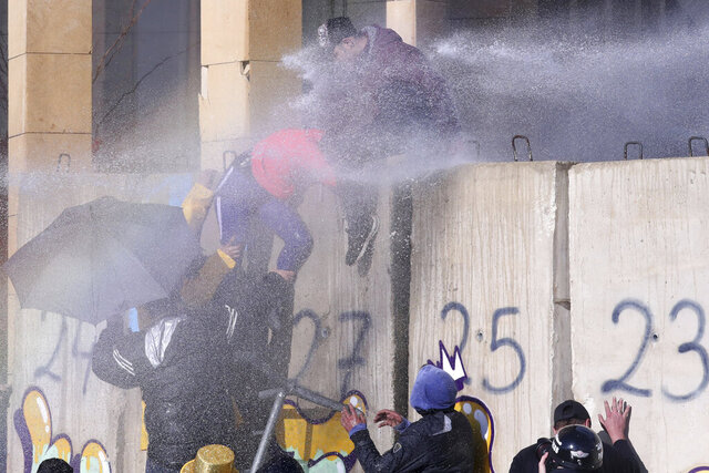 Riot police spray anti-government protesters with water cannons during a protest against a parliament session preparing a vote of confidence for the new government in downtown Beirut, Lebanon, Tuesday, Feb. 11, 2020. (AP Photo/Bilal Hussein)