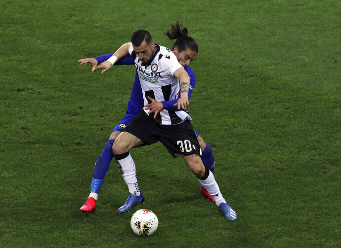 FILE - In this March 8, 2020 file photo, Fiorentina's Martin Caceres and Udinese's Ilija Nestrovski, foreground, vie for the ball during the Italian Serie A soccer match between Udinese and Fiorentina, at the Dacia Arena stadium in Udine, Italy.  Udinese president Giampaolo Pozzo recalled that the team was quarantined, after learning that Fiorentina -- the team it faced on March 8 a day before the league was suspended -- had three players who tested positive for COVID-19. (Andrea Bressanutti/LaPresse via AP)