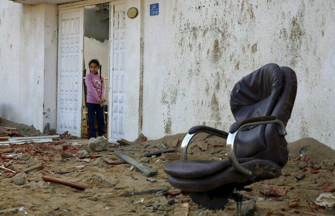 A Palestinian girl looks out from her family house at the damage the offices of Hamas leader Ismail Haniyeh, in Gaza City, Tuesday, March 26, 2019. A tense quiet took hold Tuesday morning after a night of heavy fire as Israeli aircraft bombed targets across the Gaza Strip and Gaza militants fired rockets into Israel in what threatened to devolve into a major conflict two weeks before the Israeli election. (AP Photo/Adel Hana)