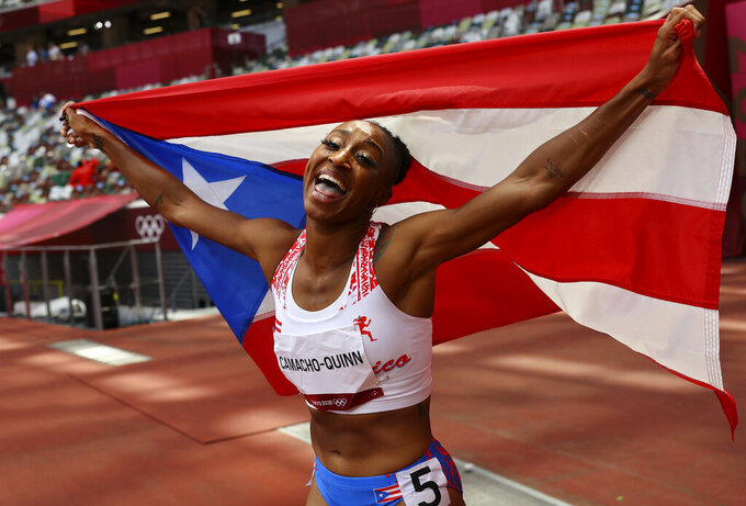 Jasmine Camacho-Quinn, of Puerto Rico celebrates after winning the gold in the women's 100-meters hurdles final at the 2020 Summer Olympics, Monday, Aug. 2, 2021, in Tokyo, Japan. (Kai Pfaffenbach/Pool Photo via AP)