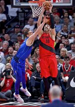 Portland Trail Blazers center Enes Kanter, right, shoots over Dallas Mavericks forward Dwight Powell during the first half of an NBA basketball game in Portland, Ore., Wednesday, March 20, 2019. (AP Photo/Craig Mitchelldyer)