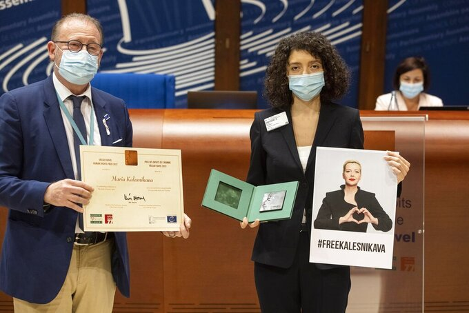 Parliamentary Assembly Rik Daems, left, holds a diploma while Tatiana Khomich holds a poster of jailed Belarus civil rights activist Maria Kalesnikava, who won the Vaclav Havel Human Rights Prize awarded at the Parliamentary Assembly of the Council of Europe, in Strasbourg, eastern France, Monday, Sept. 27, 2021. (AP Photo/Jean-Francois Badias)