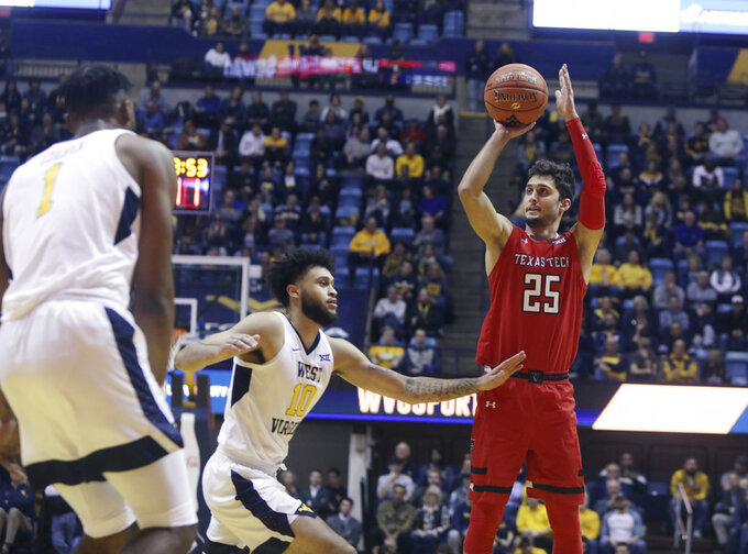 Texas Tech guard Davide Moretti (25) shoots while defended by West Virginia guard Jermaine Haley (10) during the first half of an NCAA college basketball game Wednesday, Jan. 2, 2019, in Morgantown, W.Va. (AP Photo/Raymond Thompson)