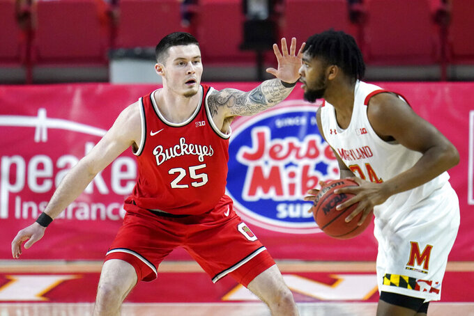 Ohio State forward Kyle Young (25) defends against Maryland forward Donta Scott during the first half of an NCAA college basketball game, Monday, Feb. 8, 2021, in College Park, Md. (AP Photo/Julio Cortez)