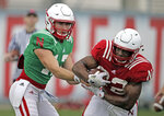 Nebraska quarterback Andrew Bunch (17) hands the ball to running back Devine Ozigbo (22) during NCAA college football fall practice in Lincoln, Neb., Wednesday, Aug. 8, 2018. Nebraska's three-man quarterback race remains too close to call. Quarterbacks coach Mario Verduzco says Adrian Martinez, Tristan Gebbia and Andrew Bunch continue to get an equal number of snaps with the first-string offense. (AP Photo/Nati Harnik)