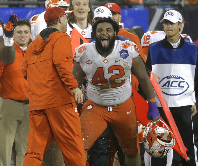 FILE - In this Saturday, Dec. 1, 2018, file photo, Clemson's Christian Wilkins (42) laughs with head coach Dabo Swinney in the closing seconds of the second half of the Atlantic Coast Conference championship NCAA college football game against Pittsburgh in Charlotte, N.C. Swinney keeps the mood light around his football program. He wants the Tigers to celebrate each victory and enjoy what it takes to get there. (AP Photo/Chuck Burton, File)