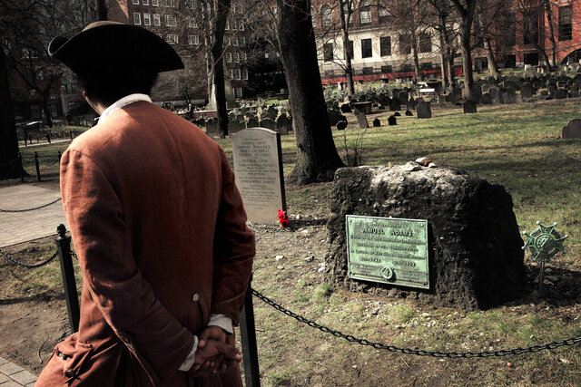 In this Tuesday, March 3, 2020 photo Samuel Ike, of Cambridge, Mass., left, dressed in the role of Revolutionary War-era African American abolitionist Prince Hall, walks past the grave with red flowers of the victims of the 1770 shooting by British soldiers, known as the Boston Massacre, at the Granary Burying Ground in Boston. The city is marking the 250th anniversary of the massacre that helped spark the Revolutionary War. The Daughters of the American Revolution is hosting a public tribute Thursday at the grave of the five victims of the violent conflict with British soldiers on March 5, 1770. The grave of founding father Samuel Adams rests at right. (AP Photo/Steven Senne)