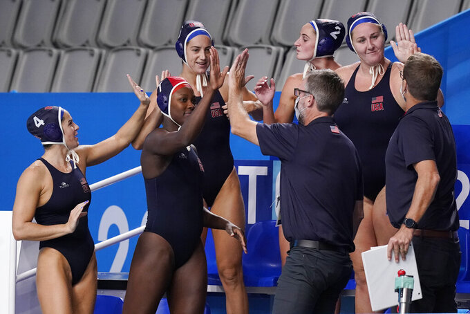 United States players and coaches celebrate following a win over Canada in a quarterfinal round women's water polo match at the 2020 Summer Olympics, Tuesday, Aug. 3, 2021, in Tokyo, Japan. (AP Photo/Mark Humphrey)