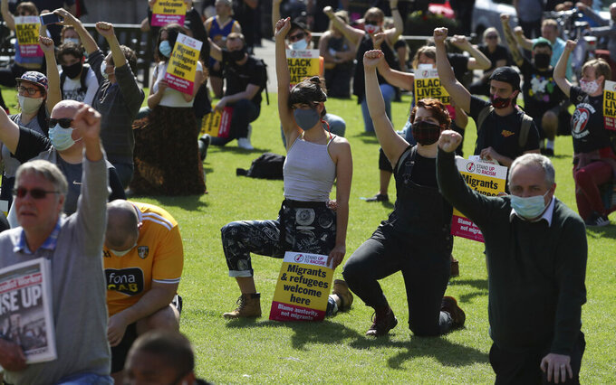 """Protesters take a knee during a Glasgow Says No to Racism event in Glasgow, Scotland, Saturday June 20, 2020.  The public gathering is aimed at """"sending a positive anti-racist message from Glasgow's George Square to the world on World Refugee Day"""" according to their public declaration.  (Andrew Milligan/PA via AP)"""