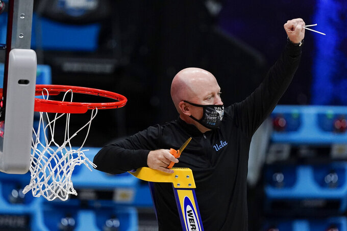 UCLA head coach Mick Cronin cuts down the net after an Elite 8 game against Michigan in the NCAA men's college basketball tournament at Lucas Oil Stadium, Wednesday, March 31, 2021, in Indianapolis. UCLA won 51-49. (AP Photo/Michael Conroy)