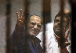 CORRECTS ATTRIBUTION OF DEATH TO ABDEL MONEIM ABDEL MAQSOUD -- FILE - In this April 21, 2015 file photo, Senior Muslim brotherhood leader Essam el-Erian, left, flashes the four-fingered symbol of Rabaah that refers to the deadly dispersal of supporters of former Egyptian President Mohammed Morsi in August 2013, inside a makeshift courtroom at Egypt's National Police Academy, in Cairo, Egypt. Abdel Moneim Abdel Maqsoud, an Egyptian lawyer said Thursday, Aug. 13, 2020 that el-Erian died of a heart attack in a Cairo prison where he was serving a 25-year sentence. The 66-year-old leader had been behind bars since 2013, following the military overthrow of Egypt's first democratically-elected president, Mohamed Morsi, who had hailed from the Brotherhood's ranks. Morsi also died while in custody. (AP Photo/Amr Nabil, File)