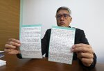 Jesus Loreto, an attorney representing Tomeu Vadell, one of six U.S. oil executives jailed for three years in Venezuela, shows a letter written by Vadell, in Caracas, Venezuela, Wednesday, Nov. 25, 2020. In the letter provided exclusively to The Associated Press on Tuesday, Nov. 24, 2020, Vadell pleads for freedom, reflects on his past and shares the pain he feels over being separated from his wife, three adult children and a newborn grandson he's never held. (AP Photo/Ariana Cubillos)