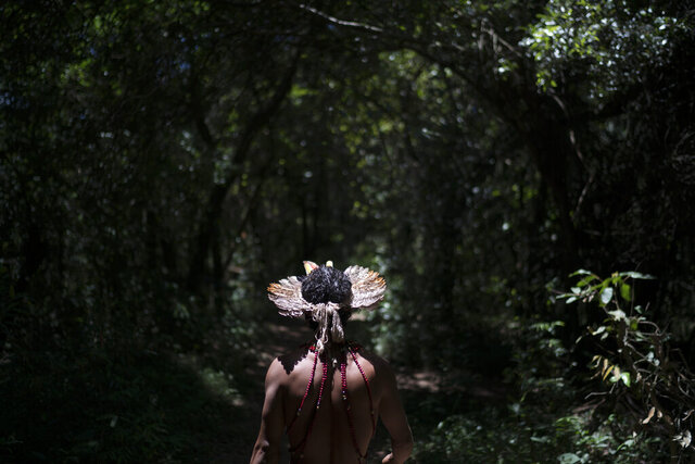 FILE - In this Jan. 29, 2019 file photo, Hayo, chief of the Pataxo Ha-ha-hae indigenous community, walks toward the Paraopeba River days after the collapse of a mining company dam, near his village in Brumadinho, Brazil. Brazil said Wednesday, Feb. 5, 20120 that it has picked a former evangelical missionary to head a body assigned to protect indigenous tribes, raising concerns among human rights activists about the tribes' health and cultural identity.  (AP Photo/Leo Correa, File)