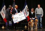 FILE - In this Jan. 30, 2016 file photo, Donald Trump, second from left, stages a check presentation with an enlarged copy of a $100,000 contribution from the Donald J. Trump Foundation to Puppy Jake, a veteran's charity, at a campaign event in Davenport, Iowa during Trump's run for president. New York Attorney General Barbara Underwood filed a lawsuit Thursday June 14, 2018, accusing Trump of illegally using his charitable foundation to pay legal settlements related to his golf clubs and to bolster his presidential campaign with Foundation disbursements such as this one in Iowa. (AP Photo/Paul Sancya, File)
