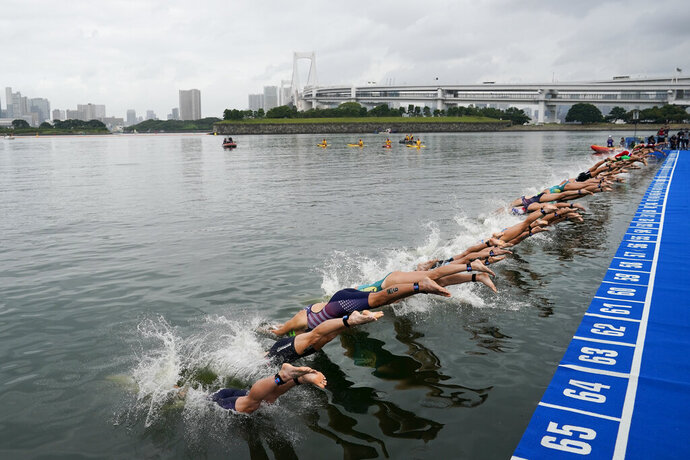 "FILE - In this Aug. 15, 2019, file photo, athletes dive into the water at the start line during a women's triathlon test event at Odaiba Marine Park, a venue for marathon swimming and triathlon at the Tokyo 2020 Olympics, in Tokyo. The IOC moved next year's Tokyo Olympic marathons and race walks out of the Japanese capital to avoid the stifling heat and humidity. Some swimmers and an 11,000-member coaching body want similar treatment: find an alternative to the distance-swimming venue in Tokyo Bay known as the ""Odaiba Marine Park.""(AP Photo/Jae C. Hong, File)"