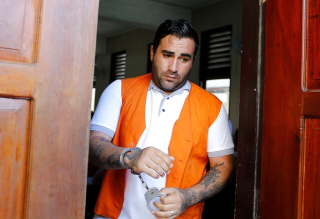 Ian Andrew Hernandez of California walks in handcuffs after his verdict trial in Bali, Indonesia on Monday, Jan. 13, 2020. An Indonesian judge has sentenced Hernandes to nine years and four months into prison for possessing and circulating 5 grams of cocaine and marijuana. (AP Photo/Firdia Lisnawati)