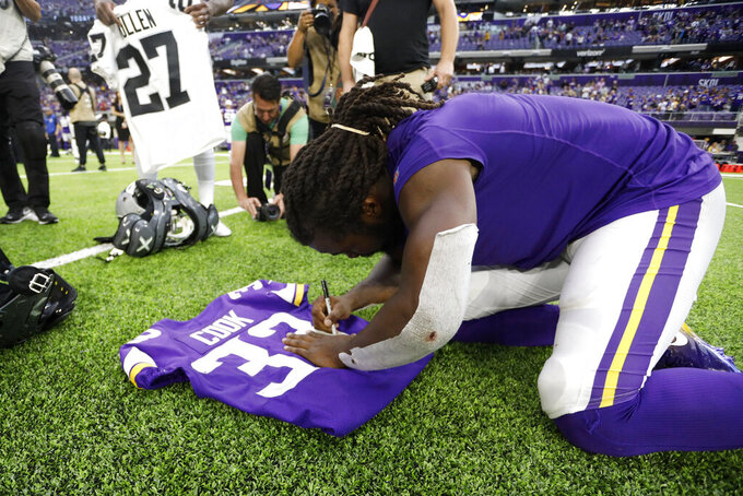 Minnesota Vikings running back Dalvin Cook autographs a jersey after an NFL football game against the Oakland Raiders, Sunday, Sept. 22, 2019, in Minneapolis. The Vikings won 34-14. (AP Photo/Bruce Kluckhohn)