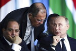 Russian President Vladimir Putin, right, listens to Russian Foreign Minister Sergey Lavrov, top, as Egyptian President Abdel Fattah el-Sisi sits next during a plenary session at the Russia-Africa summit in the Black Sea resort of Sochi, Russia, Thursday, Oct. 24, 2019. (Valery Sharifulin, TASS News Agency Pool Photo via AP)